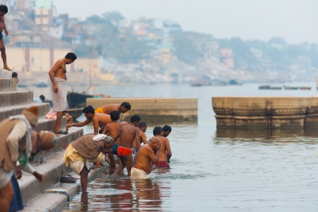 VARANASI, INDIA - JANUARY 25, 2008: Unidentified hindu men go for a group morning bath, an important cultural tradition, in the holy Ganges river on January 25, 2008 in Varanasi, India