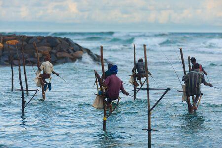 UNAWATUNA, SRI LANKA - MAY 22, 2008: Unidentified Sri Lankan stilt fishermen sit on stilts above the water to traditionally catch small fish from the ocean on May 22, 2008 in Unawatuna, Sri Lanka