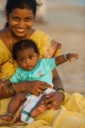 middle class: Palolem, INDIA - 29 de mayo de 2008: Una madre bien vestida y su beb� se sienta en una playa el 29 de mayo de 2008 en Palolem, India. Un auge en la riqueza de la clase media ha impulsado el turismo interno en la India Editorial