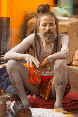 sadhu: VARANASI, INDIA - JANUARY 26, 2008: An unidentified naga baba sadhu sits on the ghat along the Ganges on January 26, 2008 in Varanasi, India. Tourism has drawn many alleged fake sadhus to Varanasi