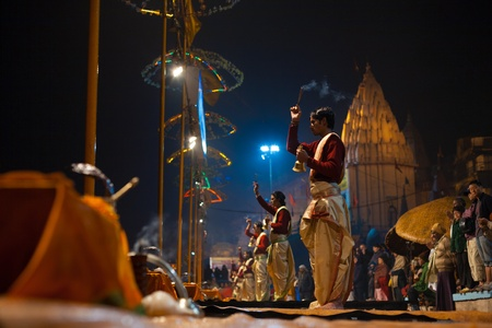 VARANASI, INDIA - JANUARY 24, 2008: A row of unidentified hindu brahmin priests lead a night puja prayer ceremony with incense sticks on the Ganges river ghats on January 24, 2008 in Varanasi, India Editorial