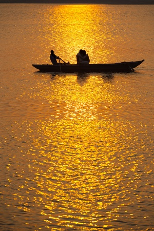 ganges: Silhouettes of Indian tourists take a sunset rowboat ride on the Ganges river in Varanasi, India