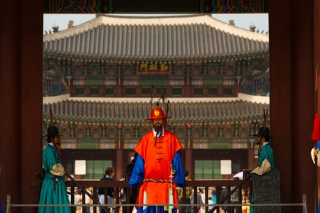 SEOUL, KOREA - SEPTEMBER 17, 2009: A guard in red traditional clothes stands at the entrance to Gyeongbokgung Palace, a national landmark, in Seoul, South Korea on September 17, 2009