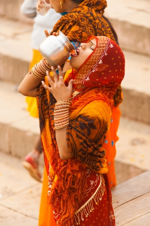 VARANASI, INDIA - JANUARY 31, 2008: An unidentified Indian woman drinks unhygenic Ganges river water from an urn following hindu custom on January 31, 2008 in Varanasi, India