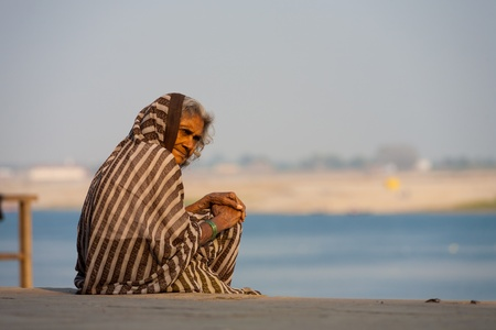 palliative: VARANASI, INDIA - JANUARY 28, 2008: An unidentified Indian woman sits on a ghat outside her hospice on January 28, 2008 in Varanasi, India. The Ganges has several hospices for those soon to pass away