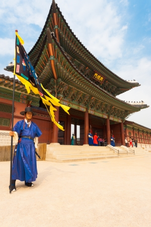 SEOUL, KOREA - SEPTEMBER 17, 2009: A flag guard in ancient blue Korean costume stands at the entry gate of Gyeongbokgung Palace, the old royal residence, in Seoul, South Korea on September 17, 2009