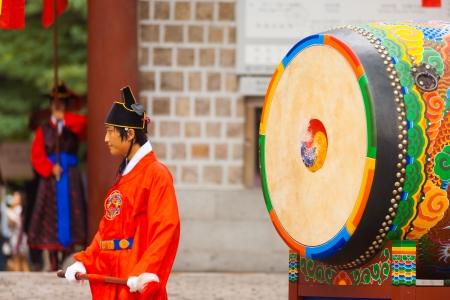 vestidos de epoca: SE�L, COREA - 27 de agosto de 2009: Un bater�a coreano tradicional con trajes de �poca espera para golpear un tambor antigua en Deoksugung Palace, un punto de referencia tur�stico, en Se�l, Corea del Sur el 27 de agosto 2009