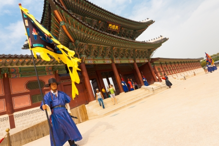 SEOUL, KOREA - SEPTEMBER 17, 2009: A flag guard in ancient blue costume stands at the entry gate of Gyeongbokgung Palace, the old royal residence, in Seoul, South Korea on September 17, 2009. Tilted