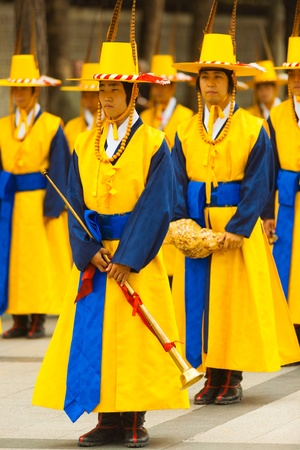 vestidos de epoca: SEÚL, COREA - 27 de agosto de 2009: músicos tradicionales coreanos en espera amarillo traje de época en la formación en Deoksugung Palace, un punto de referencia turístico, en Seúl, Corea del Sur en 27 de agosto 2009