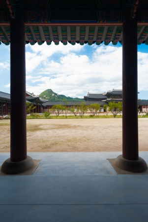 Columns support the colorful eaves in the dirt courtyard of Gyeongbokgung Palace, a tourist attraction, in Seoul, South Korea