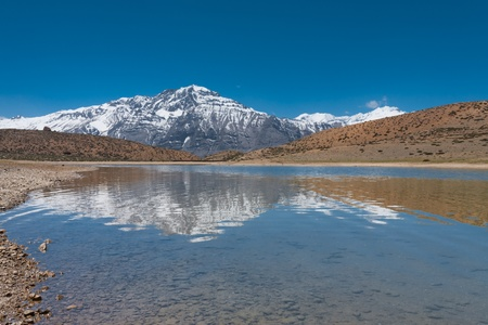 A pristine, clear alpine lake reflects a beautiful snowcapped mountain in the himalayas near the town of Dhankar, Himachal Pradesh, India
