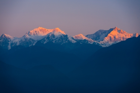 The peak of Kangchenjunga mountain, the third highest mountain in the world, glow red as it catches the colors of a morning sunrise seen from Darjeeling, India Stock Photo