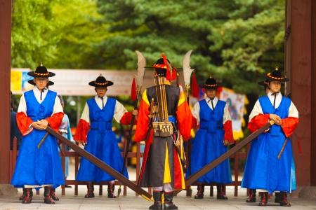 vestidos de epoca: SE�L, COREA - 27 de agosto de 2009: Soldados armados en guardia per�odo traje la puerta de entrada al Palacio Deoksugung, un hito tur�stico, en Se�l, Corea del Sur en 27 de agosto 2009
