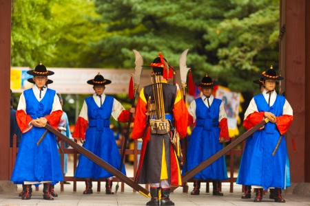 period costume: SEOUL, KOREA - AUGUST 27, 2009: Armed soldiers in period costume guard the entry gate at Deoksugung Palace, a tourist landmark, in Seoul, South Korea on August 27, 2009 Editorial