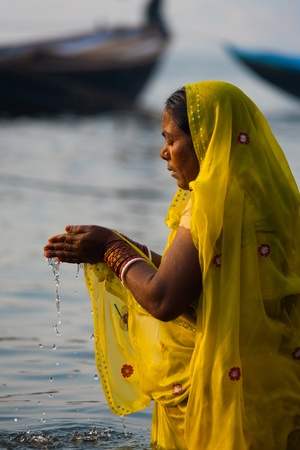 ganges: VARANASI, INDIA - JANUARY 29, 2008: A devout hindu woman cups water in her hands in prayer and bathes, an important cultural tradition, in the holy Ganges river on January 29, 2008 in Varanasi, India