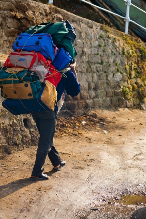 carrying: DARJEELING, INDIA - DECEMBER 26, 2007: An unidentified Indian man porter carries a heavy load on December 26, 2007 in Darjeeling, India. Unskilled laborers are left behind in Indias economic boom