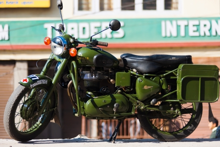 enfield: GANGTOK, INDIA - JANUARY 10, 2008: A green Enfield Bullet 350, a cult classic British motorcycle brand, is parked on a Gangtok street on January 10, 2008 in Gangtok, Sikkim, India Editorial