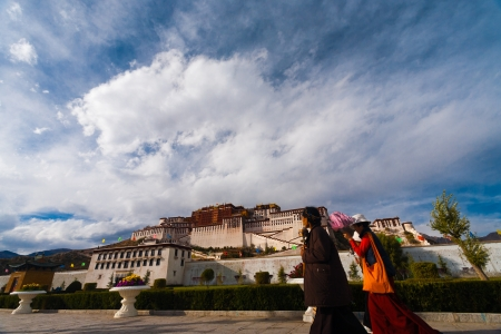 potala: LHASA, CHINA - OCTOBER 17, 2007: Two unidentified Tibetan pilgrims walk in front at the base of the Potala Palace, a major tourist site in Tibet on October 17, 2007 in Lhasa, China