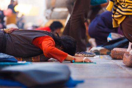 LHASA, CHINA - OCTOBER 17, 2007: An unidentified Tibetan prostrator lies flat on her stomach at Jokhang temple, a famous tourist, pilgrimage site in Tibet on October 17, 2007 in Lhasa, China Stock Photo - 19169728