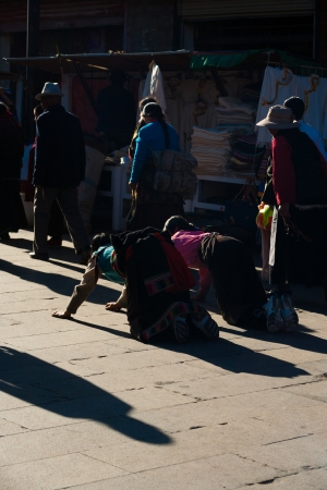 LHASA, CHINA - OCTOBER 18, 2007: Unidentified traditional Tibetans bend while prostrating at Jokhang temple, Barkhor, a famous tourist, pilgrimage site in Tibet on October 18, 2007 in Lhasa, China Stock Photo - 19169735