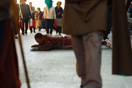 sideways: LHASA, CHINA - OCTOBER 17, 2007: An unidentified Tibetan pilgrim man prostrates his way around Jokhang temple, Barkhor, a famous tourist, pilgrimage site in Tibet on October 17, 2007 in Lhasa, China