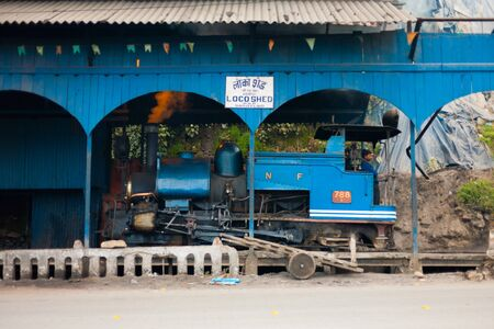 toy train: DARJEELING, INDIA - DECEMBER 27, 2007: An unidentified Indian driver stands in a parked toy train engine, a tourist attraction, in its shed on December 27, 2007 in Darjeeling, India