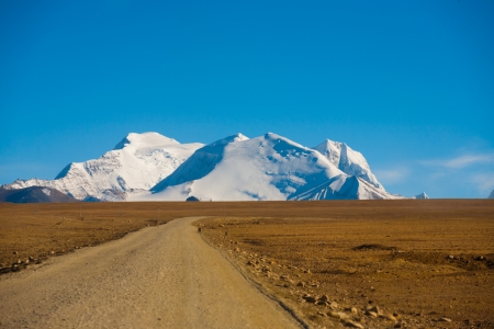 A snowcapped mountain tip of the himalayas is seen behind a curving empty barren dirt road at the border of Nepal and Tibet