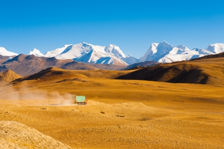 A truck drives through the barren landscape of the mountainous border between Tibet and Nepal as snowcapped himalayan mountain peaks poke through in the distance