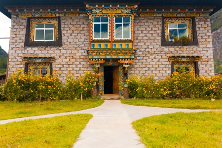 tibetan house: The beautifully decorated front of a traditional Tibetan stone brick house surrounded by a lawn and fresh flowers in Bomi, Tibet, China