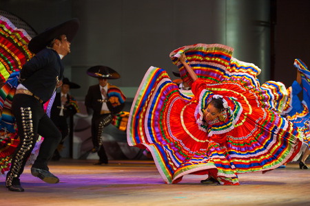 swirling: SEOUL, KOREA - SEPTEMBER 30, 2009: A female Mexican dancer spins her colorful traditional dress in front of her partner at a traditional folkloric dance performance at city halls open-air stage Editorial