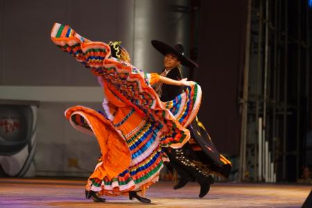 SEOUL, KOREA - 2009 년 9 월 30 일 : 미확인 된 여성 댄서 시청에서 공공 야외 무대에서 전통 민속 쇼에서 멕시코 모자 춤을하는 동안 그녀의 화려한 오렌지