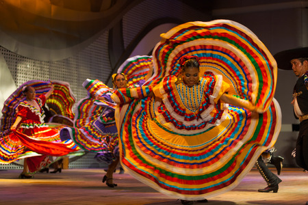 SEOUL, KOREA - SEPTEMBER 30, 2009: An unidentified female Mexican dancer spins and spreads her colorful yellow dress during a traditional folk show at a public outdoor stage at city hall