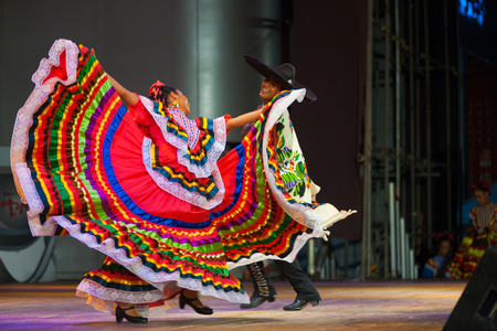 of cultural: SEOUL, KOREA - SEPTEMBER 30, 2009: A traditional Mexican Jalisco dancer spreads her colorful red dress in front of her partner during a folk show at a public outdoor stage at city hall