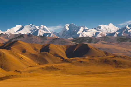 Peaks of the himalayas poke through the beautiful natural landscape of the barren mountainous terrain at the himalayan border between Nepal and Tibet