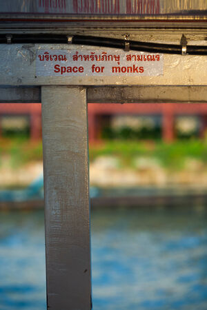 reverence: A sign on a public transportation boat in Bangkok reads Space for Monks showing the public reverence of buddhism in Thai society Stock Photo