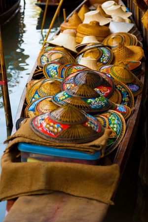 Many colorful wicker hats in a traditional conical asian style are stored in a boat at the famous tourist destination of Damoen Saduak floating market in Thailand Reklamní fotografie
