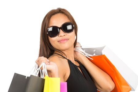 Close up portrait of gorgeous Asian female shopper in sunglasses, black dress holding colorful department store bags over both shoulders