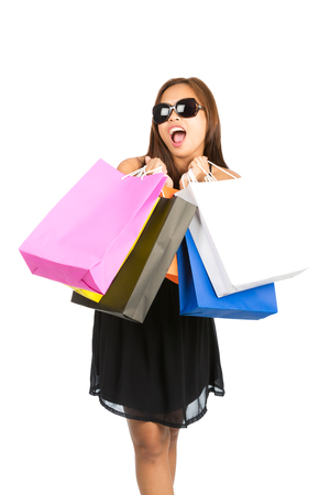A cute Asian girl shopper in black dress, stylish sunglasses, playfully mouthing words with open mouth, holds raised department store shopping bags in front. Thai national of Chinese origin. Vertical Stock Photo