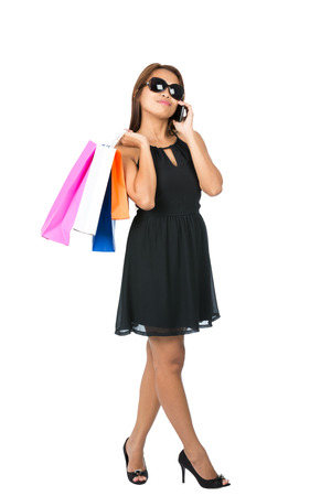 A hip Asian woman casually drapes department store shopping bags over shoulder wearing stylish black dress, sunglasses, head tilted talking on cell phone looking away. Thai national of Chinese origin photo