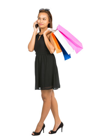 Profile of elegant Asian woman in stylish black dress takes a break from shopping to talk on mobile phone while holding department store bags. Thai national of Chinese origin. Full length photo