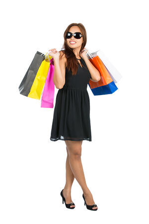looking away from camera: An elegant Asian female shopper in black dress, shoes, sunglasses flings many department store shopping bags over both shoulders while looking away from camera. Isolated. Thai national Chinese origin