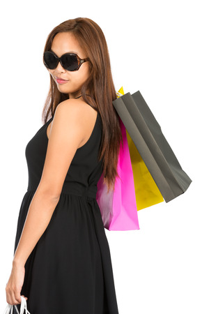 The rear of a stylish Asian female shopper facing away and colorful shopping bags looking back over her shoulder. Isolated white half length