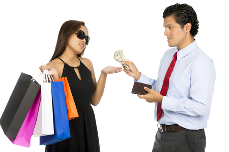demanding: A latino husband gives more cash to his demanding superficial Asian wife holding shopping bags and wearing stylish clothes holding her hand out. H