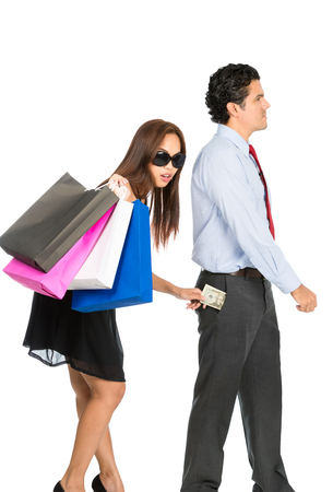 sexy couple black background: A shopaholic, greedy Asian wife with sunglasses, department store bags, steals money unnoticed from the pants pocket of her husband as he walks away