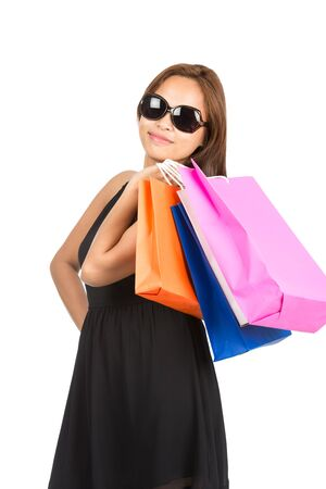 cute attitude: A cute sassy Asian woman with attitude in sunglasses smiling with colorful department store shopping bags slung over shoulder facing camera. isolated on white. Thai national of Chinese origin Stock Photo