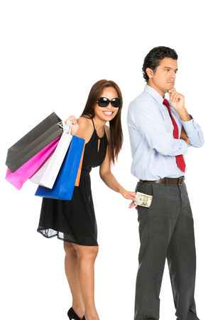 secretly: A playful smiling female shopper with store shopping bags secretly removing money unnoticed from her pushover husband pants pocket while he is looking away V