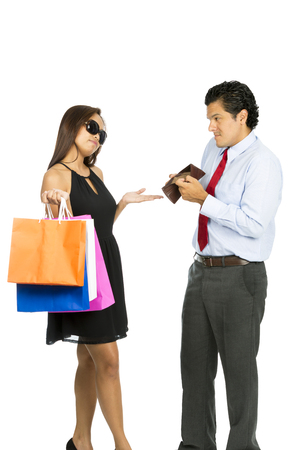 demanding: A greedy shopaholic gold digger superficial wife shrugging and demanding cash from her poor husband showing his empty wallet with no money. V Stock Photo