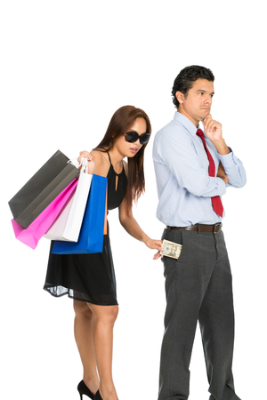 secretly: A beautiful shopaholic wife with stylish dress, sunglasses, department store bags secretly inserting saved money back into unaware husband pants pocket