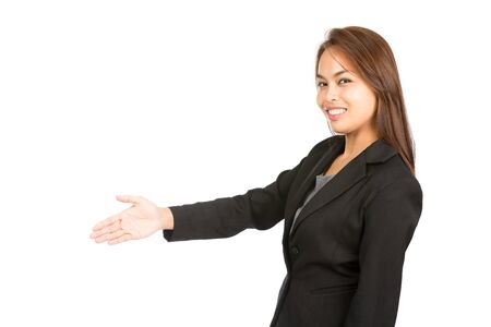side profile: Side view profile of light brown haired Asian woman in black business clothes smiling greeting, offering handshake turning head looking at camera on deal.
