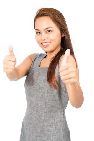 approving: A cute Asian girl with light brown hair in gray sleeveless dress enthusiastic in approving with two thumbs up giving validation, recognition, blessing or compliment.